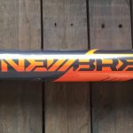 An orange and black DeMarini Newbreed bat laying on a wooden deck
