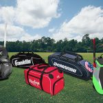 Five different softball bags in a grassy field